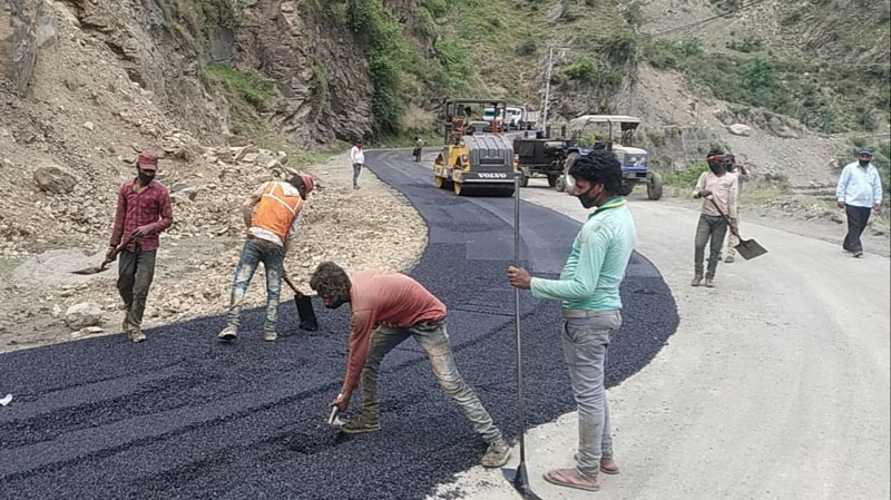 Workers engaged in blacktopping work. -Excelsior/Rafi Choudhary
