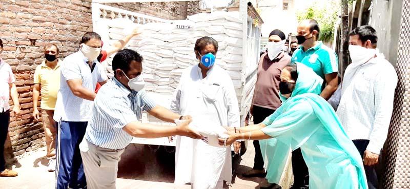 Senior Congress leader Raman Bhalla distributing ration among poor in Gandhi Nagar constituency.