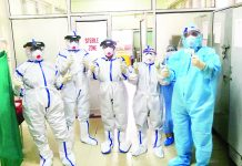 Corona warriors donning full PPE kits pose at Government Hospital, Gandhi Nagar, Jammu.