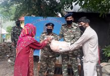CRPF personnel providing ration to needy persons. -Excelsior/Parvaiz