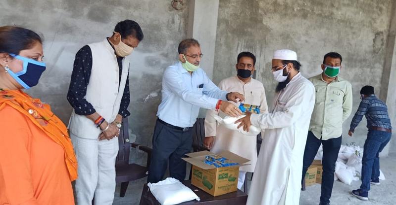 Former Dy CM Kavinder Gupta distributing ration in Masjid Mohalla Bahu on Thursday.