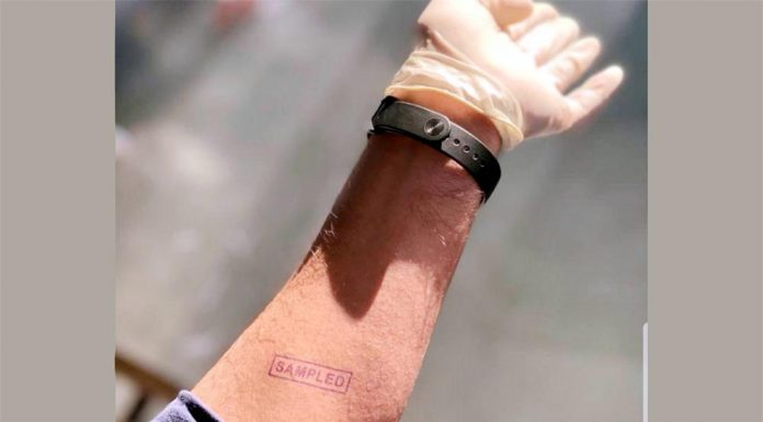 A man showing his arm ink marked as 'sampled' after his sample was taken at a collection centre on arrival at Jammu Tawi Railway Station on Friday. (UNI)