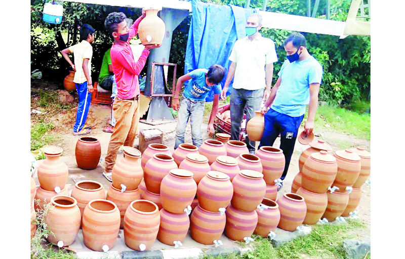 People purchasing tap fitted earthen pots from a roadside vendor in Jammu. (UNI)
