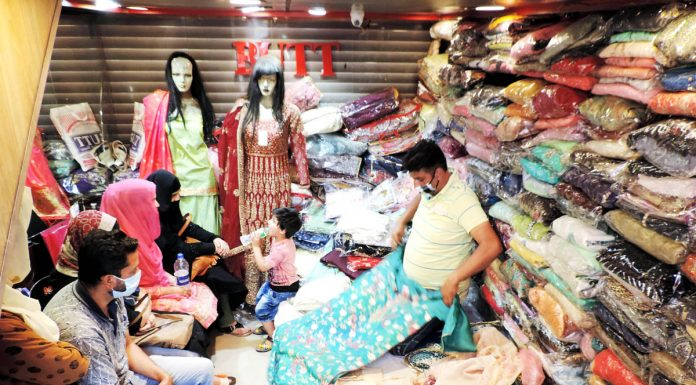 Masked customers in a garment shop at Lal Chowk in Srinagar on Monday.(UNI)