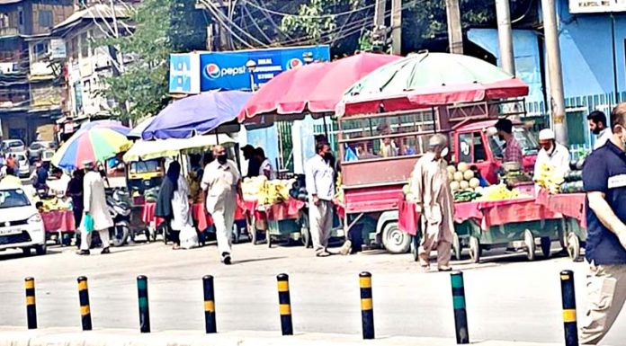 Roadside vendors establish their business just outside the COVID-19 dedicated Chest Disease hospital in Dalgate area of Srinagar on Wednesday.(UNI)