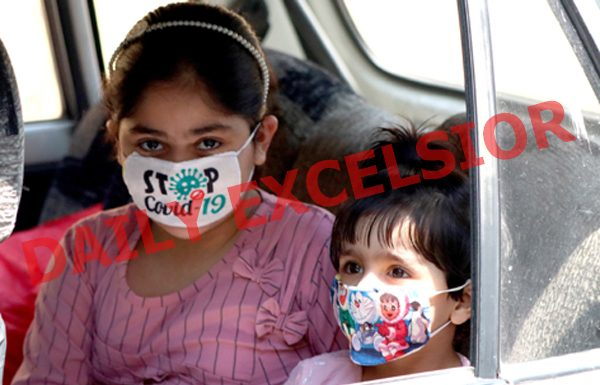 Children travelling in a car wearing masks in Srinagar on Sunday. — Excelsior/Shakeel