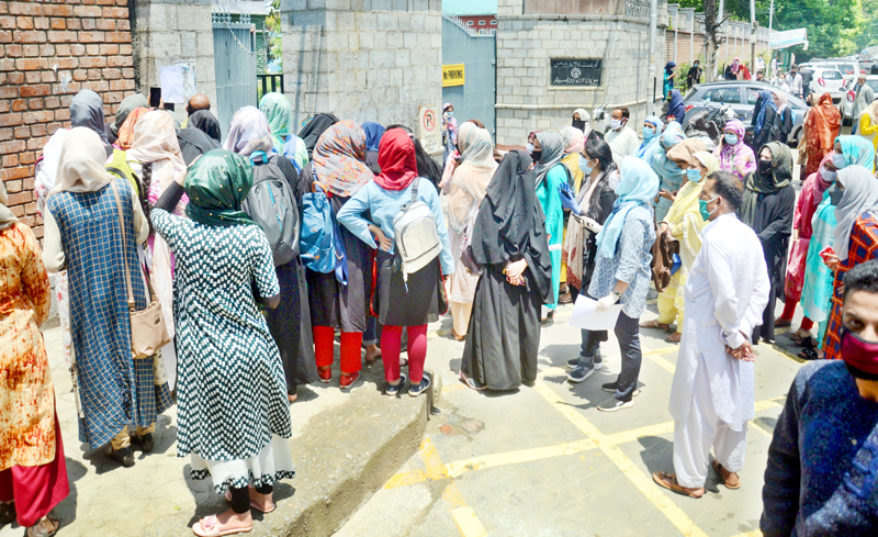 Students wait outside the Women's College in Srinagar. -Excelsior/Shakeel