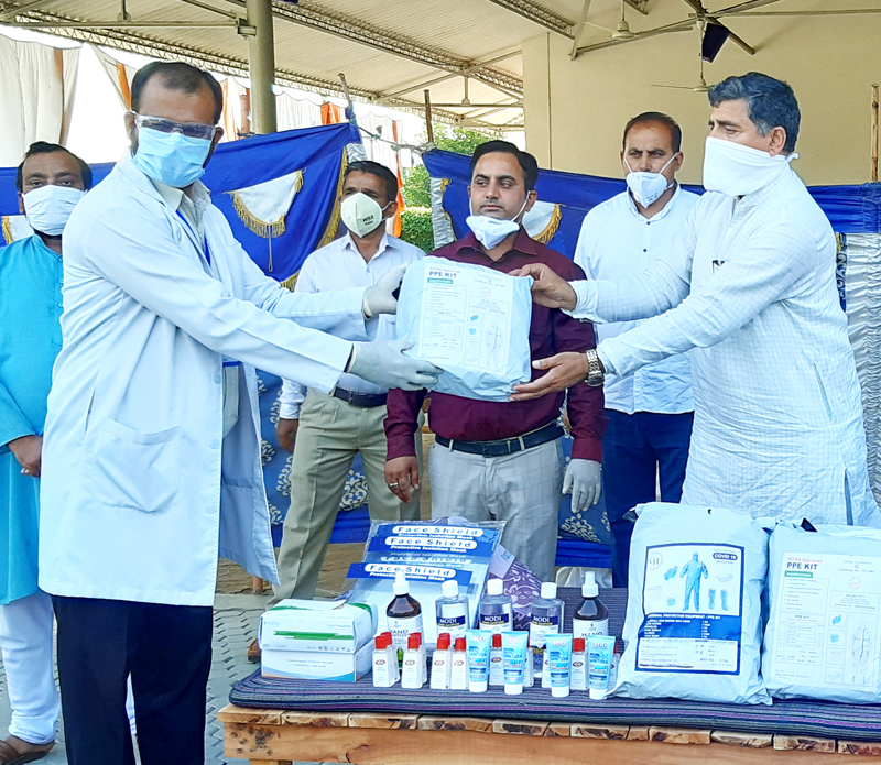 MP, Jugal Kishore Sharma distributing PPE Kits and Sanitizers at Quarantine Centre Arnia on Wednesday.