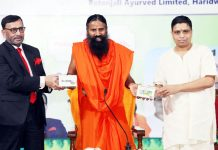 Yog Guru Swami Ramdev with Achariya Balakrishna launching Divya Corona kit which will be effective to cure of COVID-19 patients as claimed by the Patanjali Research Institute, in Haridwar on Tuesday. (UNI)