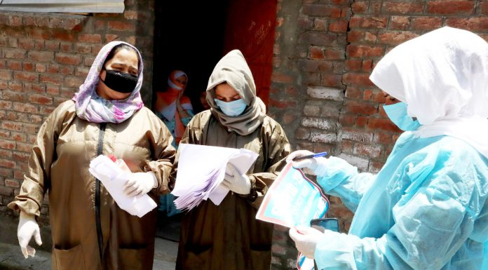 Health workers carrying out mandatory contact tracing, surveillance after COVID-19 +ve cases were detected in Srinagar. —Excelsior/Shakeel