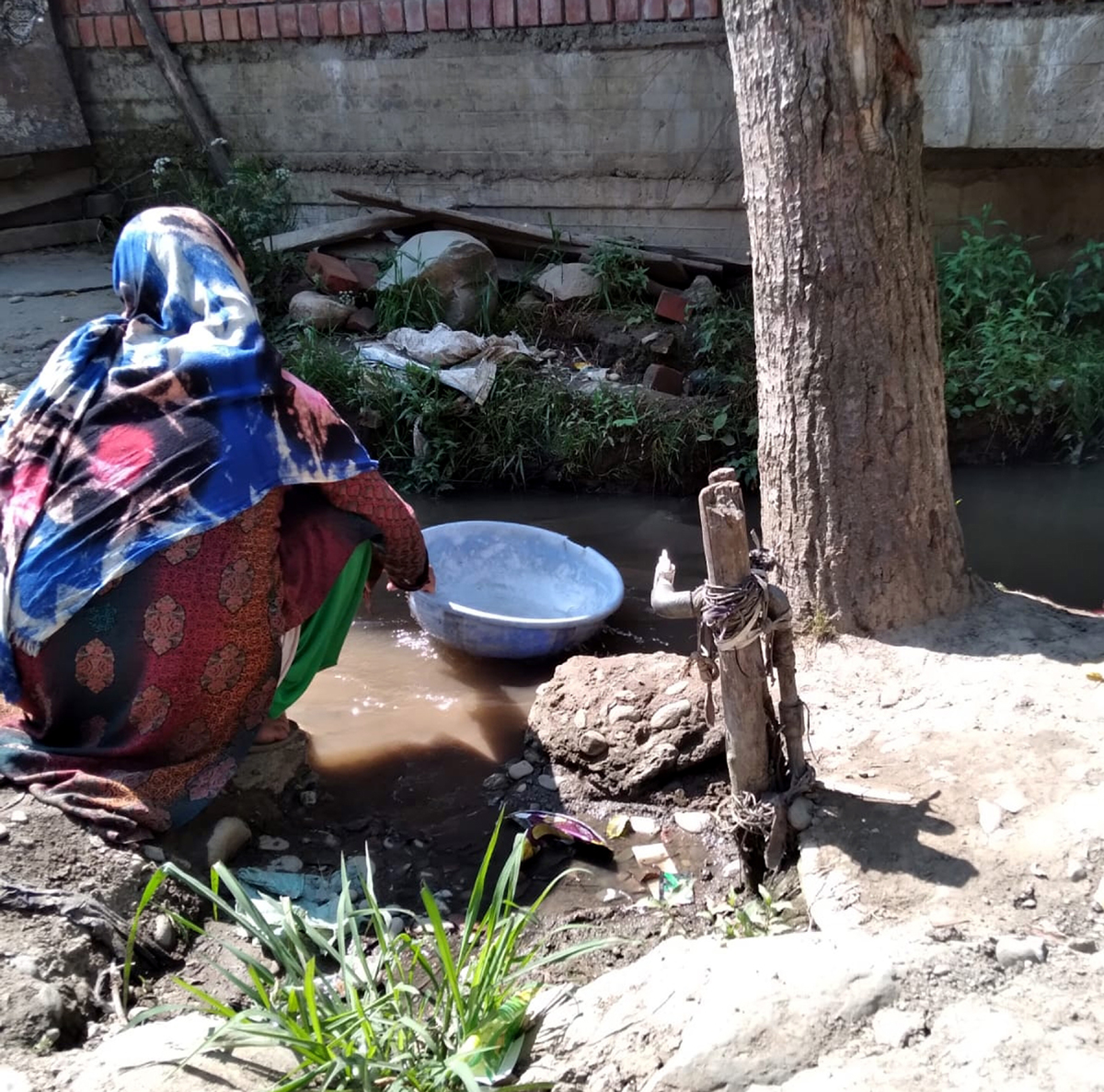 A woman sitting near a dry tap in a Pattan village.