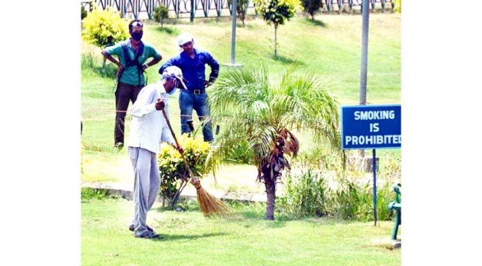 Workers cleaning Maharaja Hari Singh Park after the Government's order of opening of all parks and gardens in Jammu on Thursday.(UNI)