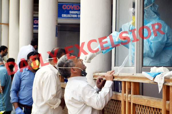 A Health worker in PPE takes a swab sample from a JK Bank employee for COVID-19 at TRC Srinagar on Thursday. —Excelsior/Shakeel