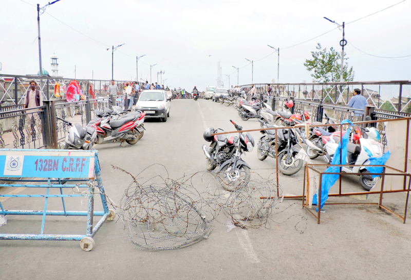 Vehicles parked on the Amirakadal bridge closed with barricades and razor wire during lockdown in Srinagar on Tuesday. (UNI)