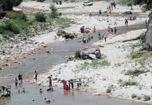 People enjoying bath to beat the heat in River Jhajjar at Jhajjar Kotli located along Jammu-Srinagar National Highway in Jammu district on Sunday. (UNI)