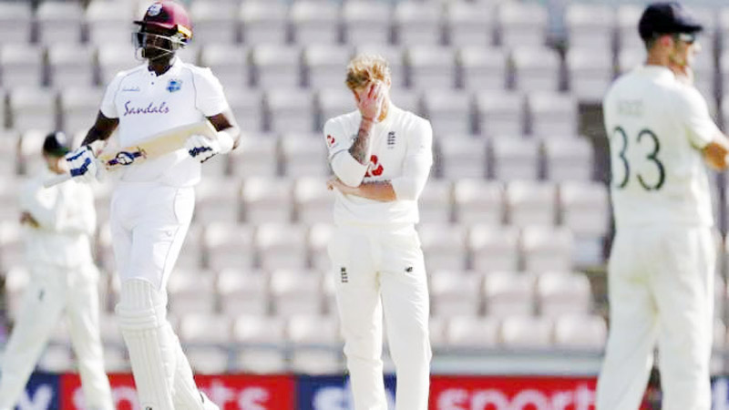 England captain Ben Stokes (center) reacts after West Indies captain Jason Holder (left) hit a boundary on his delivery during the fifth day of the first cricket Test match between England and West Indies at the Ageas Bowl in Southampton, England on Sunday.