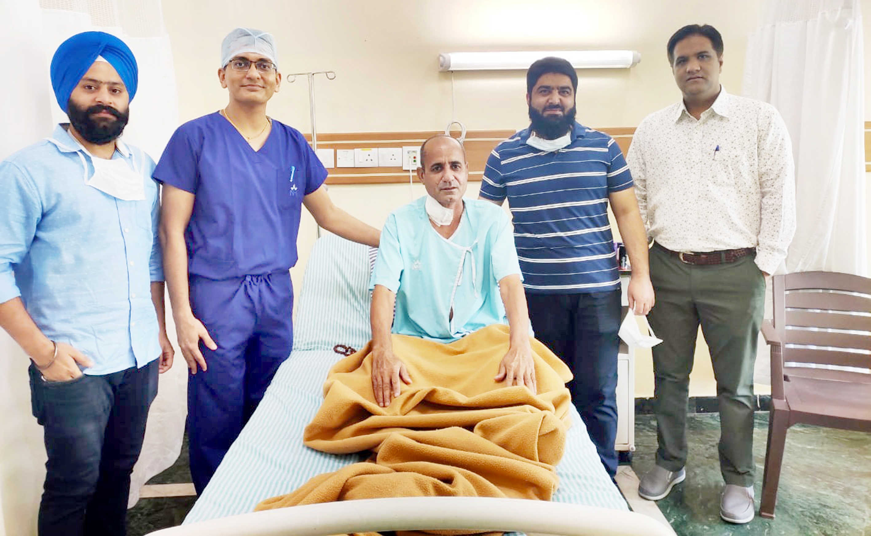 A team of doctors posing with a patient on whom they performed a complex surgery at SMVD Narayana Super Speciality Hospital, Katra.