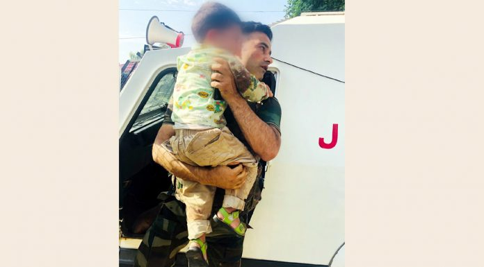 SHO Sopore takes child to safety after his grandfather was killed at Model Town Sopore on Wednesday. —Excelsior/Aabid Nabi