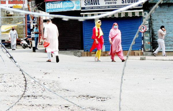 Concertina razor wires laid to close road at Budshah Chowk bylane as people walk past by a closed market in Srinagar on Wednesday. (UNI)