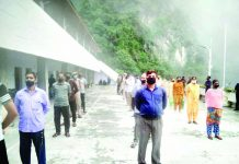 Staff and security personnel wait for their turn for COVID-19 testing at Mata Vaishno Devi Bhawan on Friday. -Excelsior/Romesh Mengi
