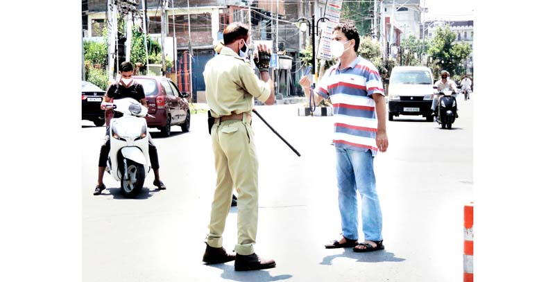 A security personnel stops a person during lockdown in Srinagar on Monday.(UNI)
