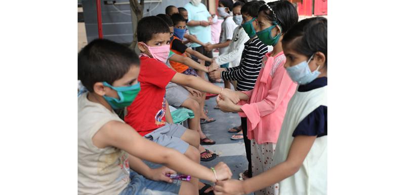 Girls in Bal Ashram Jammu tying Rakhi to boys on the occasion of Rakshabandhan on Monday. —Excelsior/Rakesh