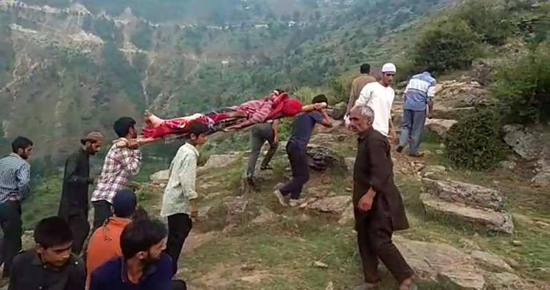 People carrying patient on wooden stretcher.
