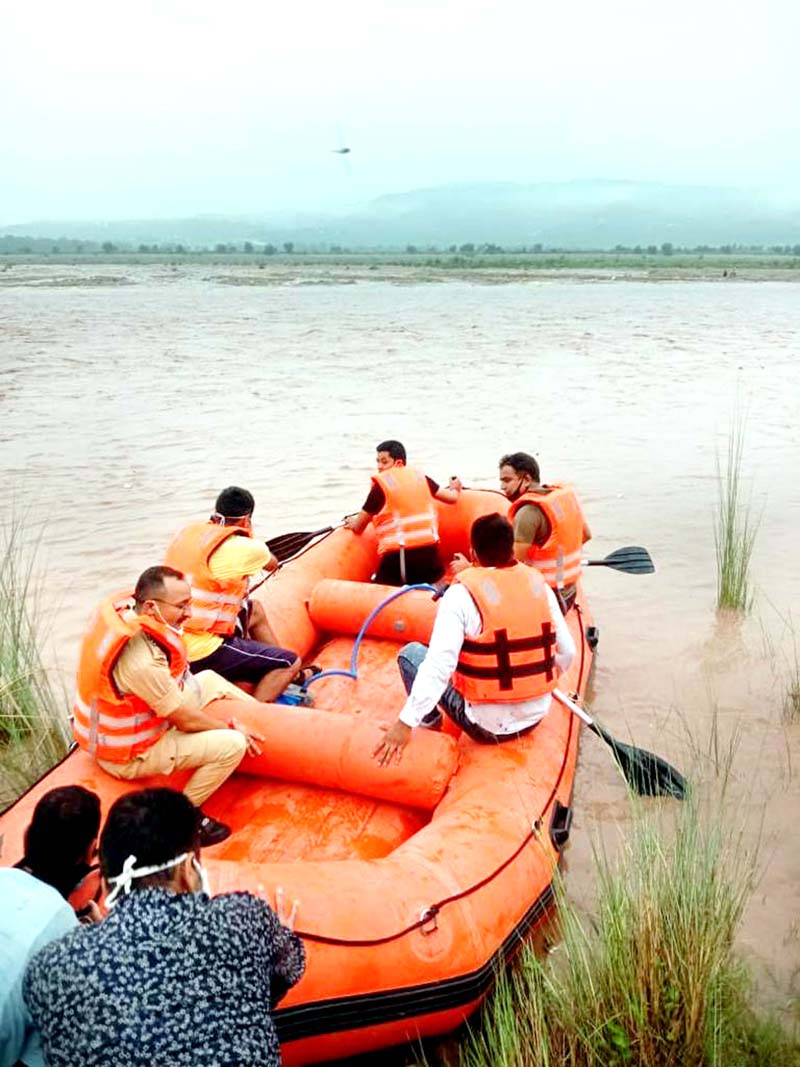 Police personnel on way to rescue two persons from river Tawi on Sunday.