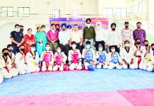 Taekwondo players along with officials posing for a group photograph along with officials at Indoor Hall of Sports Stadium, Poonch.