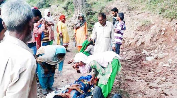 Villagers evacuating injured persons after accident at Gharian Dhanas in Chenani on Saturday.