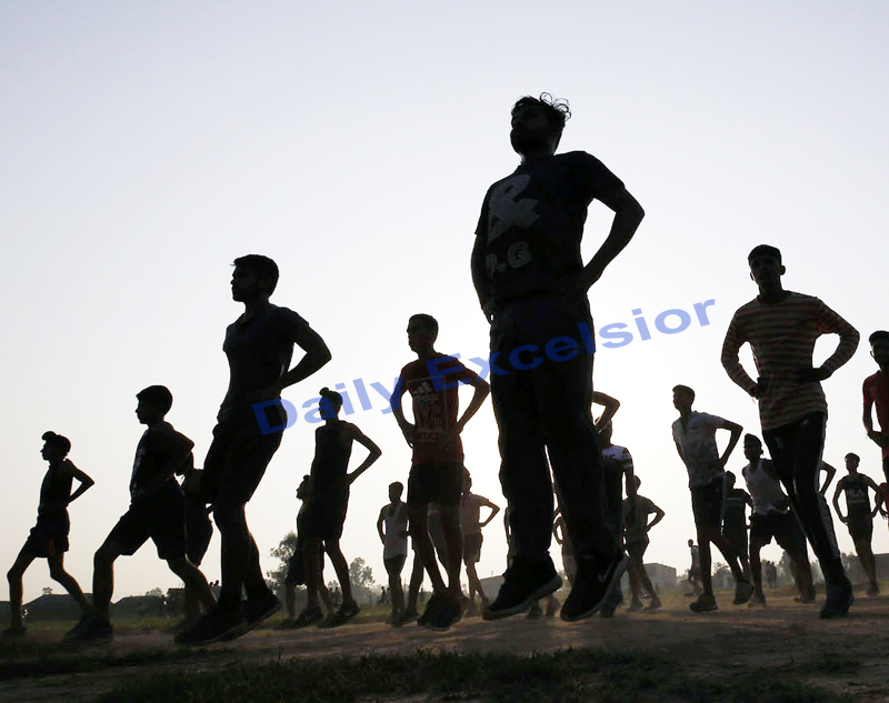 Youngsters perform exercises early in the morning as part of preparations for recruitment in security forces on the outskirts of Jammu. -Excelsior/Rakesh