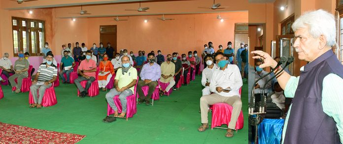 Lieutenant Governor Manoj Sinha interacting with residents of Jagti migrant township on Monday.