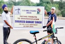 Retired Marine Commando, Kuldeep Kumar displaying poster of Bhagat Singh during cycle run on Sunday.