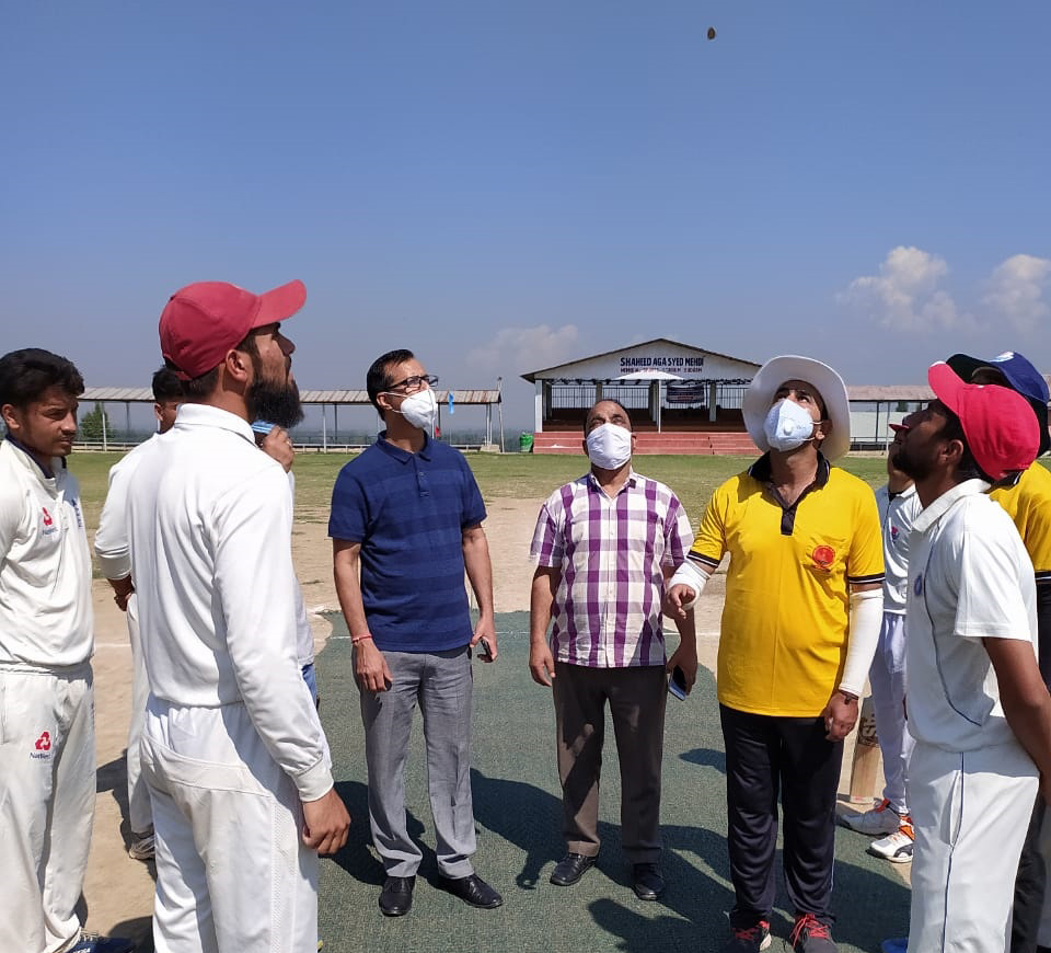 Captains of participating teams in Inter Zonal District Level Cricket Tournament tossing coin before start of match at Budgam Sports Stadium.