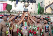 Winners of Dangal (Wrestling competition) posing for a group photograph with winning trophy at Anantnag.