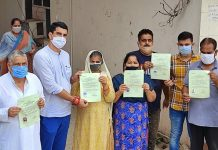 Tehsildar Jammu West Rajesh Baru giving domicile certificates to the applicants.