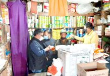 A team of officers checking quality and prices of essential commodities at a shop in Kargil town.