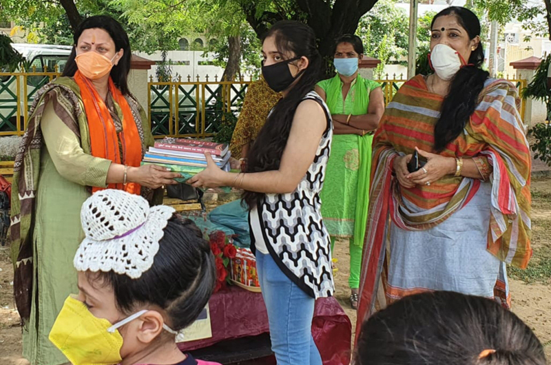 BJP secretary, Rekha Mahajan distributing note books among students at Jammu on Wednesday.