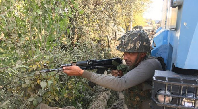 A soldier takes position during encounter at Chakoora, Shopian on Wednesday. —Excelsior/Younis Khaliq