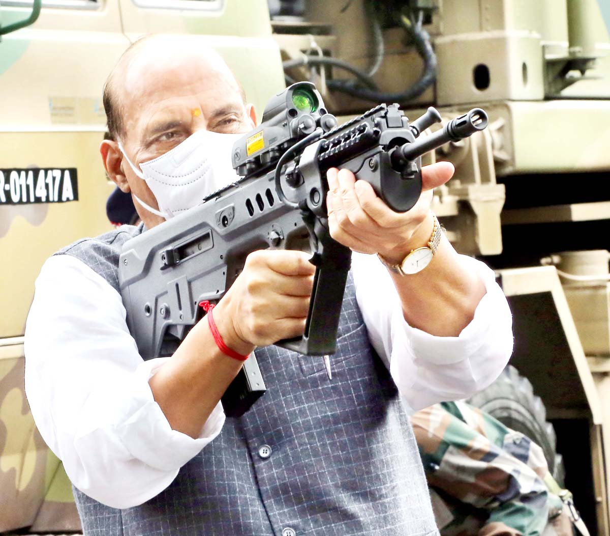 Defence Minister Rajnath Singh trying his hand on a rifle during Shastra Puja at Sukna War Memorial in Darjeeling on Sunday. (UNI)