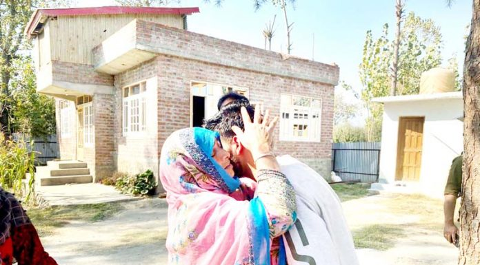 A woman hugs her son as he surrendered before Army and police in Sopore on Thursday. -Excelsior/Abid Nabi