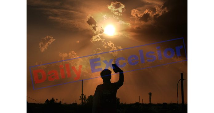 A girl takes picture as Sun sets in Jammu. -Excelsior/Rakesh