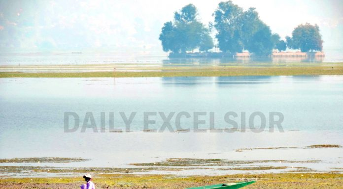 A man sitting in a boat fishing in the middle of famous Dal lake in Srinagar on Friday. (UNI)