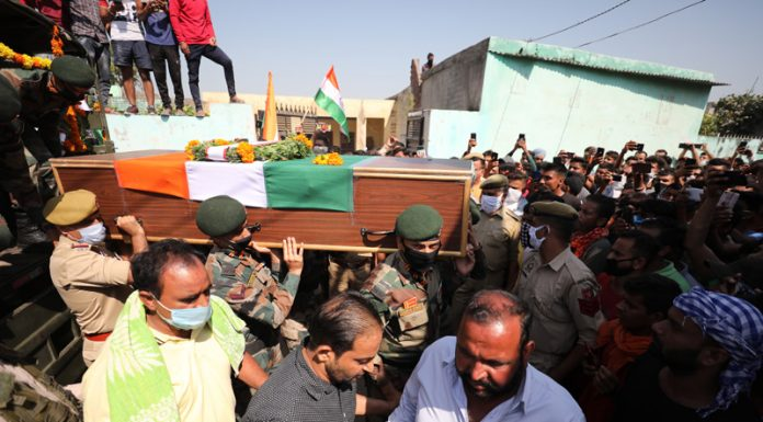 People raising slogans in praise of martyred jawan as his body reaches native village in RS Pura, Jammu on Friday. -Excelsior/Rakesh
