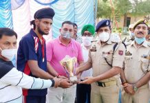 Dignitaries of the event presenting winning trophy to players at Pouni.