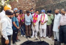 Chairman, JMC, Baldev Singh Billawaria kick starting black topping of road in Ekta Vihar on Friday.
