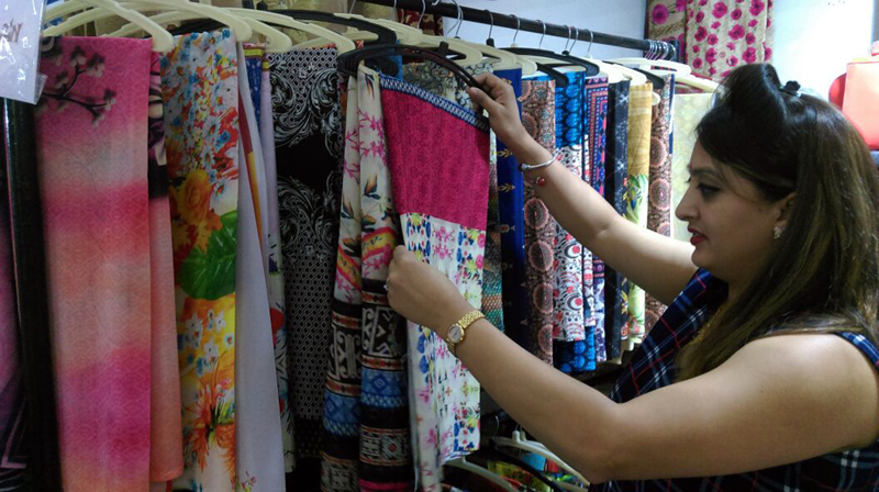 A lady selecting a dress at an exhibition by Silk & Cotton Fab in Jammu.