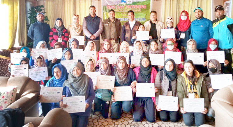 Women trekkers posing for a group photograph with certificates along with dignitaries at Gulmarg. Excelsior/Basharat Ladakhi
