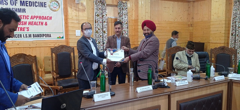 Director ISM J&K Dr Mohan Singh awarding an AYUSH officer in Srinagar.