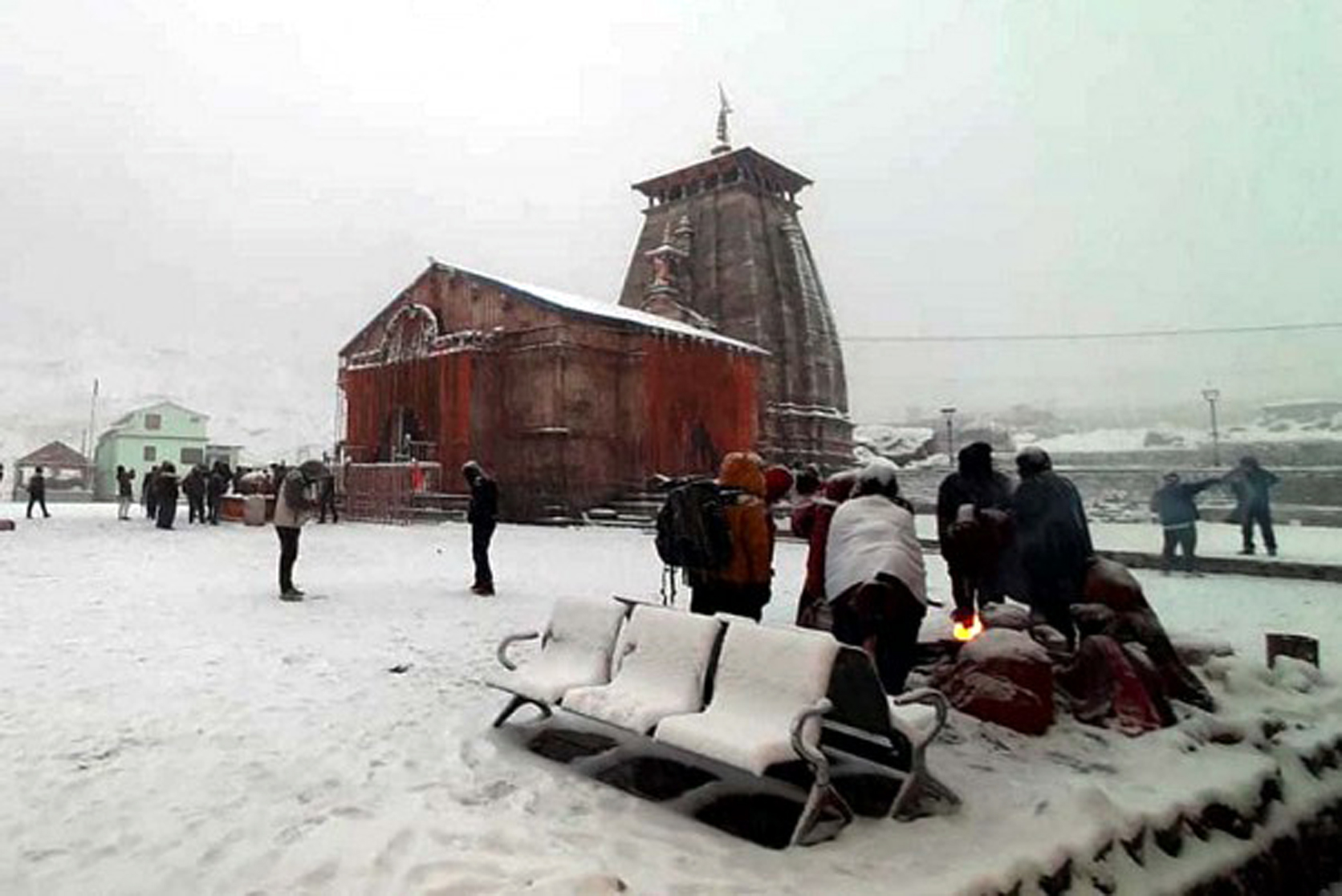 People warm themselves near a bonfire during snowfall at Kedarnath Dham in Uttarakhand. The portals of the shrine are being closed for the winter season from today.